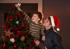 Muchacho de ayuda del papá para adornar el árbol de navidad fotografía de archivo libre de regalías