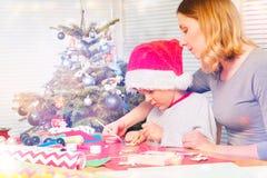 Muchacho de ayuda del profesor para adornar el ornamento de la Navidad imagen de archivo