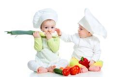 Muchacho y muchacha de bebés con las verduras Fotos de archivo