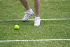 Muchacho de bola que persigue la pelota de tenis imagen de archivo libre de regalías