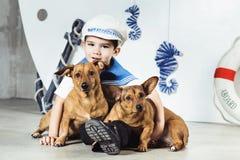 Muchacho de cabina con dos pequeños perros delante de la nave imágenes de archivo libres de regalías