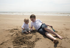 Muchacho de diez años con su hermano del bebé que juega en la playa Imagenes de archivo