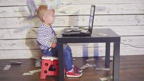 Muchacho de dos años con un ordenador y un dinero que cae muchacho sonriente que se sienta en la tabla con los billetes de banco  almacen de video