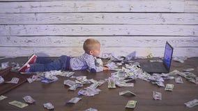 Muchacho de dos años con un ordenador y un dinero muchacho sonriente que se sienta en la tabla con los billetes de banco del orde almacen de metraje de vídeo
