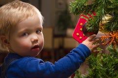Muchacho de dos años que adorna el árbol de navidad Fotos de archivo