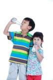 Muchacho de dos asiáticos y leche de consumo de la muchacha, en blanco Leche de consumo FO Foto de archivo libre de regalías