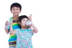 Muchacho de dos asiáticos y leche de consumo de la muchacha, en blanco Leche de consumo FO Fotografía de archivo libre de regalías