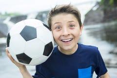 Muchacho de dos jóvenes al aire libre con la sonrisa del balón de fútbol Imágenes de archivo libres de regalías