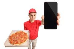 Muchacho de entrega adolescente de la pizza que muestra un teléfono Fotografía de archivo