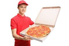Muchacho de entrega adolescente de la pizza que muestra una pizza dentro de una caja Imágenes de archivo libres de regalías