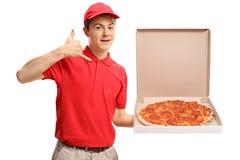 Muchacho de entrega adolescente de la pizza que sostiene una caja de la pizza y que hace una llamada Foto de archivo libre de regalías