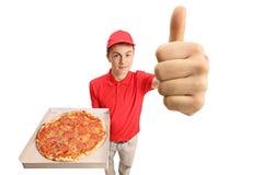 Muchacho de entrega adolescente de la pizza que sostiene una pizza y que hace un pulgar para arriba Imágenes de archivo libres de regalías