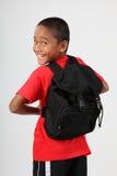 Muchacho de escuela alegre que mira detrás sobre su hombro Fotografía de archivo