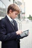 Muchacho de escuela con la tablilla electrónica Imagenes de archivo