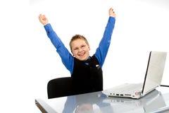 Muchacho de escuela divertido con la computadora portátil aislada en blanco Imagenes de archivo