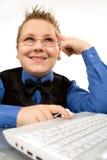 Muchacho de escuela divertido con la computadora portátil aislada en blanco Imágenes de archivo libres de regalías