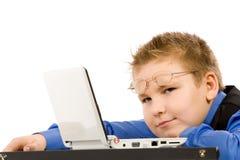 Muchacho de escuela divertido con la computadora portátil aislada en blanco Fotos de archivo libres de regalías