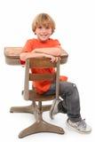 Muchacho de escuela en escritorio Imagen de archivo libre de regalías