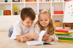 Muchacho de escuela que enseña su hermana a cómo leer Fotografía de archivo libre de regalías