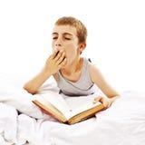 Muchacho de escuela que lee un libro en su cama Imagen de archivo libre de regalías
