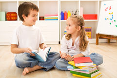 Muchacho de escuela que muestra a su pequeña hermana cómo leer fotos de archivo libres de regalías