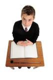 Muchacho de escuela que se sienta en el escritorio de la escuela Imágenes de archivo libres de regalías