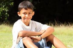 Muchacho de escuela que se sienta en el parque en día asoleado Imagen de archivo libre de regalías