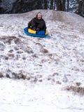Muchacho de griterío entonado de la imagen que monta un trineo abajo de una cuesta escarpada con nieve e hierba Imágenes de archivo libres de regalías