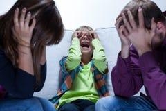 Muchacho de griterío y padres cansados Imágenes de archivo libres de regalías