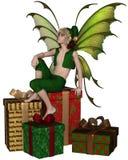 Muchacho de hadas del duende de la Navidad que se sienta en una pila de presentes Fotografía de archivo libre de regalías