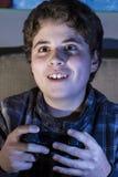 Muchacho de la diversión con la palanca de mando que juega al juego de ordenador en casa. Imagenes de archivo