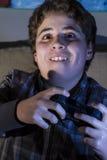 Muchacho de la diversión con la palanca de mando que juega al juego de ordenador en casa. Fotografía de archivo libre de regalías