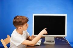 muchacho de la Escuela-edad que se sienta con el ordenador portátil del monitor en el estudio Fotos de archivo
