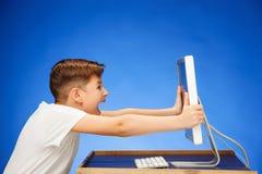 muchacho de la Escuela-edad que se sienta delante del ordenador portátil del monitor en el estudio Foto de archivo libre de regalías