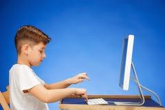 muchacho de la Escuela-edad que se sienta delante del ordenador portátil del monitor en el estudio Imagen de archivo