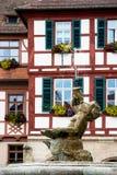Muchacho de la estatua de la fuente y casa bávara en Schwabach imagenes de archivo
