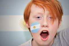 Muchacho de la fan del pelirrojo con la bandera argentina pintada en su cara Foto de archivo libre de regalías