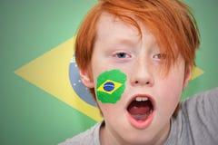 Muchacho de la fan del pelirrojo con la bandera brasileña pintada en su cara Imagen de archivo libre de regalías