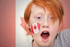 Muchacho de la fan del pelirrojo con la bandera canadiense pintada en su cara Imágenes de archivo libres de regalías