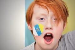 Muchacho de la fan del pelirrojo con la bandera canaria pintada en su cara Foto de archivo libre de regalías
