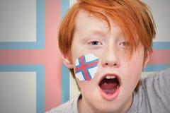 Muchacho de la fan del pelirrojo con la bandera de Faroe Island pintada en su cara Foto de archivo libre de regalías