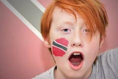 Muchacho de la fan del pelirrojo con la bandera de Trinidad and Tobago pintada en su cara Imagen de archivo