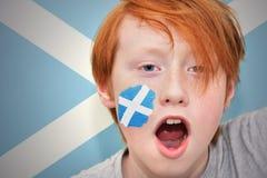 Muchacho de la fan del pelirrojo con la bandera escocesa pintada en su cara Imágenes de archivo libres de regalías