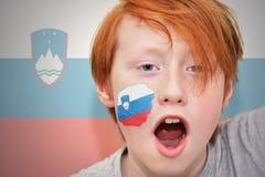 Muchacho de la fan del pelirrojo con la bandera eslovena pintada en su cara Fotografía de archivo