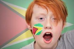 Muchacho de la fan del pelirrojo con la bandera guyanesa pintada en su cara Imagen de archivo