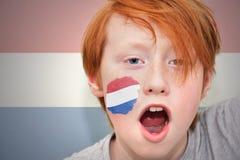 Muchacho de la fan del pelirrojo con la bandera holandesa pintada en su cara Foto de archivo