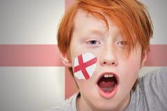 Muchacho de la fan del pelirrojo con la bandera inglesa pintada en su cara Imagenes de archivo