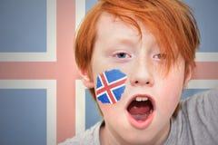 Muchacho de la fan del pelirrojo con la bandera islandesa pintada en su cara Imagen de archivo