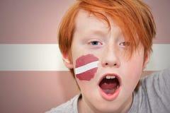 Muchacho de la fan del pelirrojo con la bandera letona pintada en su cara Foto de archivo libre de regalías
