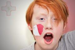 Muchacho de la fan del pelirrojo con la bandera maltesa pintada en su cara Fotografía de archivo libre de regalías